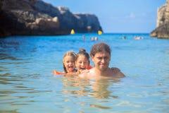O pai e duas filhas estão tendo o divertimento na praia foto de stock