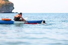 O pai e a filha asi?ticos s?o de ensino e de forma??o o protetor ou o salvamento de vida na praia imagens de stock