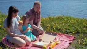 O pai e a filha da m?e comem a pizza pelo mar da costa vídeos de arquivo