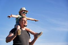 O pai e a filha em ombros exultam felizmente paizinho que guarda pouca filha que senta em indicações o voo do papa imagem de stock royalty free