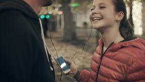 O pai e a filha escutam a música em fones de ouvido na rua filme