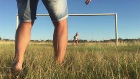 O pai e a filha felizes jogam com a bola no campo verde com porta do futebol Família alegre que joga o futebol video estoque