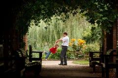 O pai e a filha no jardim na planta escavam um túnel Foto de Stock Royalty Free