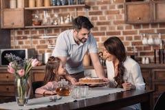 O pai e a filha que apresentam a mãe endurecem para o feriado do dia do ` s da mãe na cozinha Fotografia de Stock Royalty Free