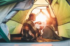 O pai e o filho bebem o chá quente que senta-se junto na barraca de acampamento fotografia de stock royalty free