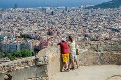 O pai e o filho contemplam a cidade de Barcelona fotos de stock