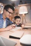 O pai e o filho estão lendo contos de fadas registram com a lupa na noite em casa imagens de stock royalty free