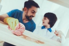 O pai e o filho limpam superfícies da mobília da poeira fotografia de stock