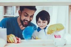 O pai e o filho limpam superfícies da mobília da poeira imagem de stock royalty free