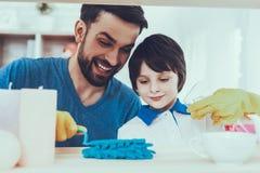 O pai e o filho limpam superfícies da mobília da poeira fotografia de stock royalty free
