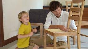 O pai e o filho montam a mobília de madeira das peças pequenas O rapaz pequeno ajuda seu pai a montar uma cadeira filme