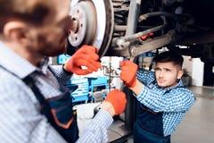 O pai e o filho trabalham no auto serviço Dois mecânicos trabalham com os detalhes do carro Fotografia de Stock Royalty Free