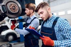 O pai e o filho trabalham no auto serviço Dois mecânicos trabalham com os detalhes do carro Imagens de Stock Royalty Free