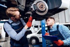 O pai e o filho trabalham no auto serviço Dois mecânicos trabalham com os detalhes do carro Imagem de Stock