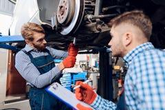 O pai e o filho trabalham no auto serviço Dois mecânicos trabalham com os detalhes do carro Fotos de Stock Royalty Free