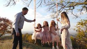 O pai e a mãe agitam suas filhas em um balanço sob uma árvore vídeos de arquivo