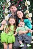 O pai e a mãe felizes com bebê e filha sentam-se no balanço Foto de Stock Royalty Free
