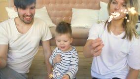 O pai e a mãe novos comemoram seus chuveirinhos ardentes do aniversário do filho em casa e sorriso filme