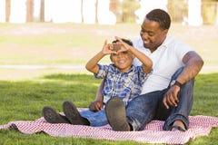 O pai e o filho da raça misturada que fazem o coração entregam o sinal Fotografia de Stock Royalty Free
