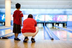 O pai e o filho esperam pacientemente para a esfera de bowling foto de stock