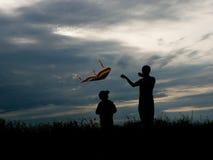 O pai e o filho lançam um papagaio Imagens de Stock Royalty Free