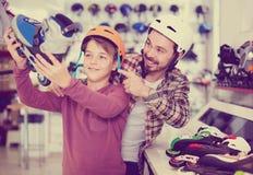 O pai e o filho que decidem em novo patinam na loja dos esportes imagens de stock royalty free