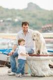 O pai e o filho sentam-se com cães em um banco perto do mar Imagens de Stock