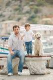 O pai e o filho sentam-se com cães em um banco perto do mar Imagem de Stock