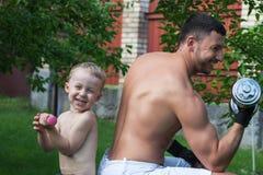 O pai e o filho treinam com dumbbells Foto de Stock Royalty Free