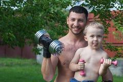O pai e o filho treinam com dumbbells Imagem de Stock Royalty Free