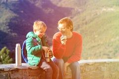 O pai e o filho viajam nas montanhas que bebem o chá quente Fotografia de Stock Royalty Free