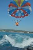 O pai e o filho voam em um paraquedas sobre o mar Imagens de Stock