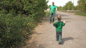 O pai e o rapaz pequeno feliz jogam com haste fora video estoque