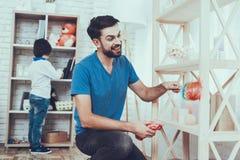 O pai e os filhos limpam superfícies da mobília da poeira fotos de stock