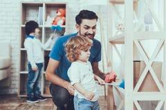 O pai e os filhos limpam superfícies da mobília da poeira imagem de stock
