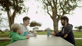 O pai e seus filhos estão sentando-se na tabela filme