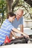 O pai ensina o filho reparar o carro imagem de stock royalty free