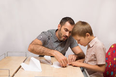 O pai ensina seu filho fazer os aviões de papel Imagens de Stock Royalty Free