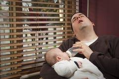 O pai esgotado alimenta o filho Imagem de Stock Royalty Free