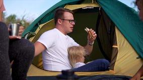 O pai está comendo o almoço com sua filha na natureza, eles está em uma barraca video estoque