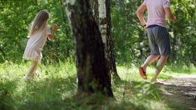 O pai está correndo com sua filha no parque do verão, lento-movimento vídeos de arquivo