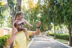 O pai está tendo o divertimento com sua filha pequena, uma caminhada, verão ho Fotos de Stock