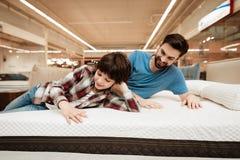 O pai farpado considerável com filho novo está testando o colchão para o softness fotos de stock royalty free