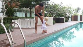 o pai faz exercícios com a filha loura pequena na associação video estoque
