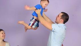 O pai feliz aumenta os braços de seu filho pequeno vídeos de arquivo