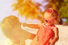 O pai feliz e a filha pequena bonito jogam na praia Foto de Stock