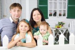O pai feliz, a mãe, o bebê e a filha pequena estão fotografia de stock