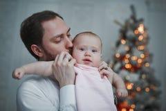 O pai feliz que abraça sua filha do bebê para a árvore de Natal ilumina-se no fundo imagem de stock