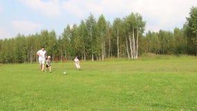 O pai, o filho e a filha felizes jogam com a bola no campo verde filme