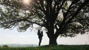 O pai guarda nas mãos sua filha e fala perto de uma árvore grande filme